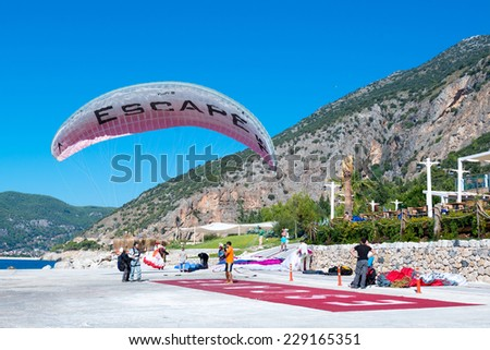 OELUEDENIZ, TURKEY - OCTOBER 20, 2014: Tandem paragliders landing in the luxurious holiday resort Lykia World on October 20, 2014 in Oeluedeniz, Turkey. Oeluedeniz is well known amongst paragliders - stock photo