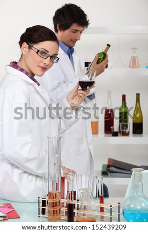 Oenologists analysing wine - stock photo