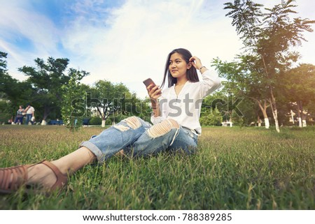 Of young happy lady sitting in park outdoors listening music while chatting. Attractive woman sitting in park talking smart phone. Beautiful girl sitting in park looking at smartphone and smiling