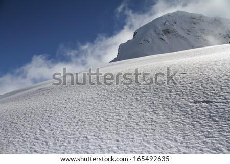 off-piste ski slope in powder snow and scenic alpine background - stock photo