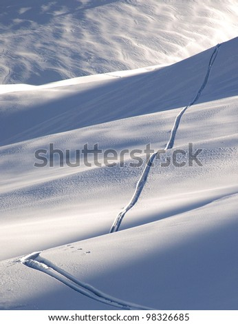 Off-piste ski track in sunset light - stock photo