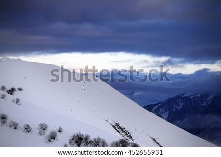 Off-piste slope and cloudy sky at sunset. Caucasus Mountains, Georgia, region Gudauri.  - stock photo