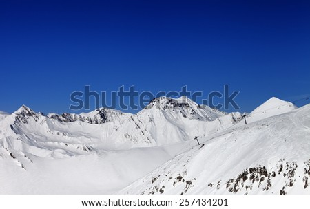 Off-piste slope and ropeway in nice sun day. Caucasus Mountains, Georgia. Ski resort Gudauri. - stock photo