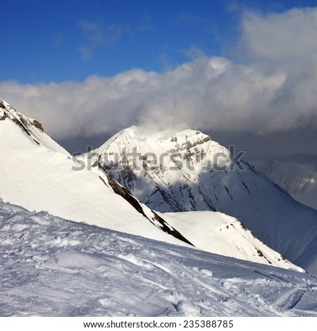 Off-piste slope and sunlit mountains at evening. Caucasus Mountains, Georgia, ski resort Gudauri. - stock photo