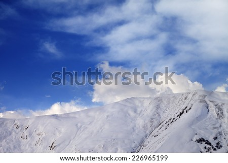 Off-piste slope at evening and sky with clouds. Caucasus Mountains, Georgia, ski resort Gudauri. - stock photo
