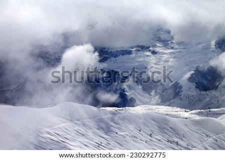 Off-piste slope in sunlight clouds. Caucasus Mountains, Georgia, ski resort Gudauri. - stock photo