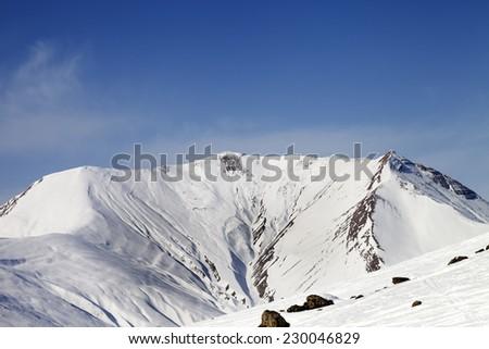 Off-piste slope with stones and snowy mountains. Caucasus Mountains. Georgia, ski resort Gudauri. - stock photo