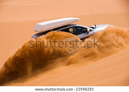 Off-road car going up the sand dune