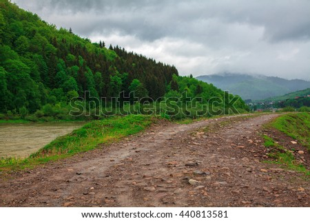 off-road in the mountains near the river in the rain - stock photo