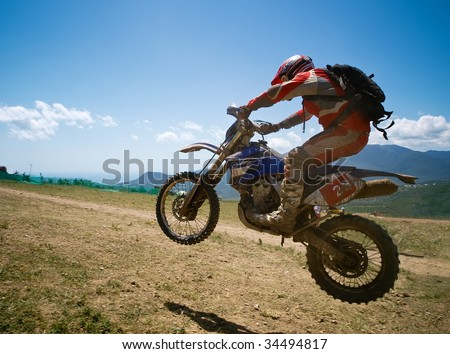 Off-road rider is jumping against a summer mountains - stock photo