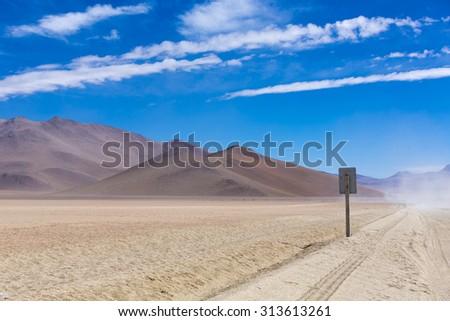 Off-road track in the Atacama desert, Bolivia with majestic colored mountains and blue sky in Eduardo Avaroa Andean Fauna National Reserve, Bolivia - stock photo