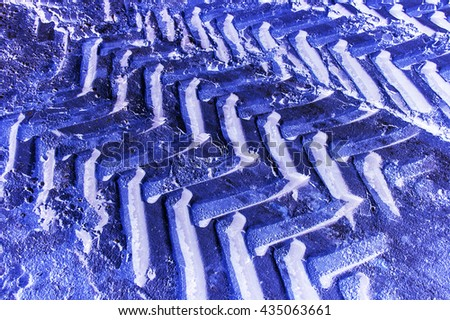 Off road tractor wheel tracks on road ice motoring background image. Industrial transport theme. - stock photo