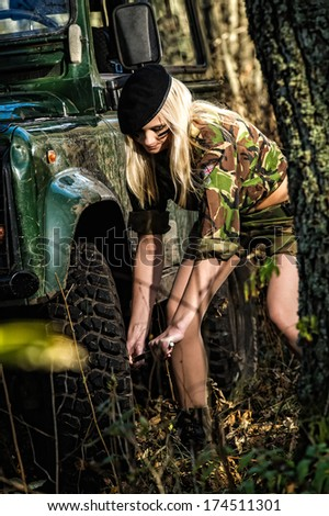Off-road vehicle and beautiful girl, she is using tyre wrench - stock photo
