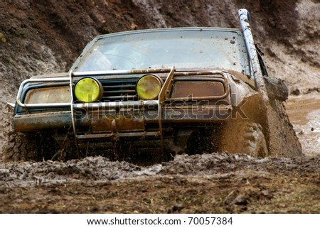 Off road vehicle coming out of a mud hole hazard - stock photo