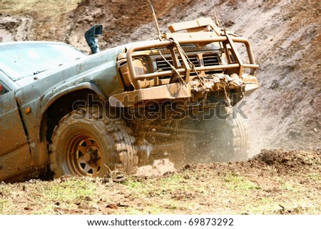 Off road vehicle coming out of a mud hole hazard. Mud and smoke around - stock photo