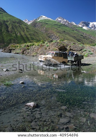 Off-road vehicle crossing the river - stock photo