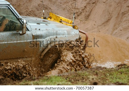 Off road vehicle going through a muddy water hazard. - stock photo