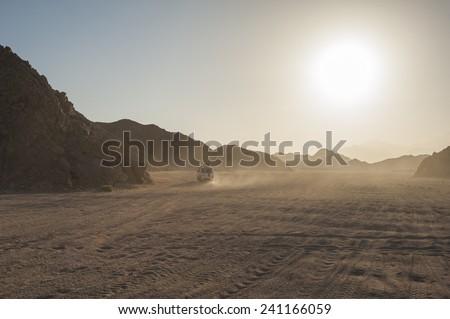 Off road vehicle on safari traveling through arid desolate desert landscape with sunset - stock photo