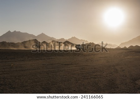 Off road 4x4 vehicle traveling on safari in remote rocky desert with sunset - stock photo