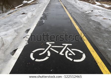 off season on wet bicycle road with snow and ice by both sides - stock photo