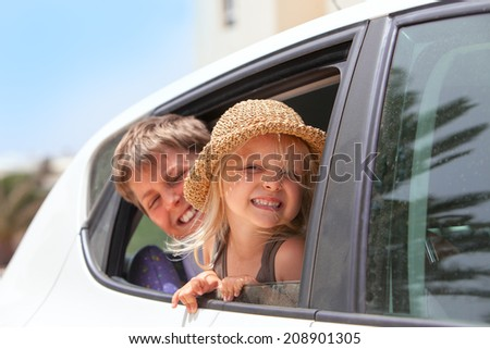 Off to the beach!   Portrait of two happy children inside the car .  - stock photo