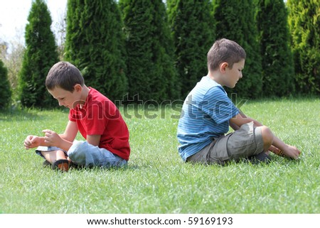Offended boys, brothers, sibling sitting back to back. - stock photo
