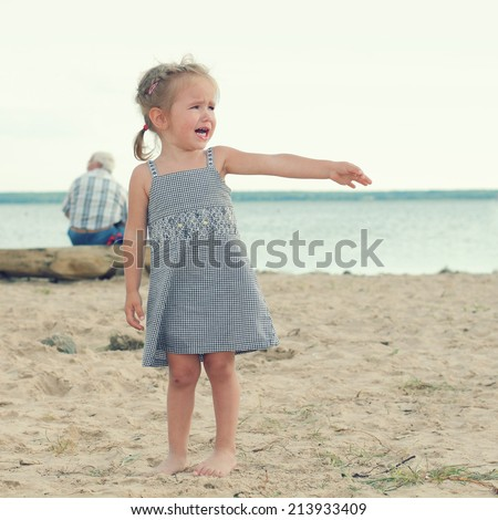 offended crying little girl on the beach. sad little girl with blond hair - stock photo
