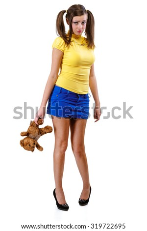 Offended girl-teenager with a teddy bear, isolated on white background. - stock photo