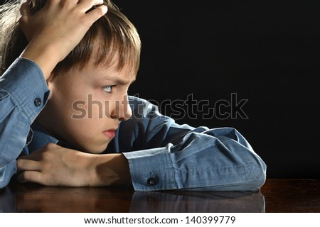 offended little boy on a black background - stock photo