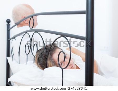 offended woman  on   bed next to   frustrated man. - stock photo