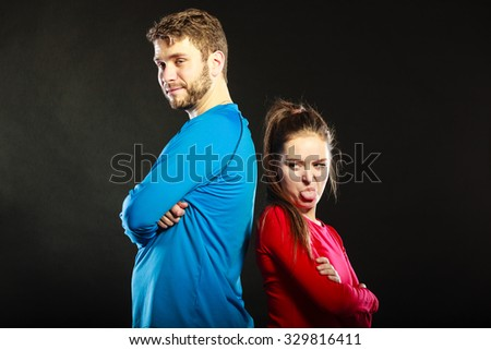 Offended young couple standing back to back after argument quarrel. Woman sticking out tongue. Disagreement in relationship. - stock photo