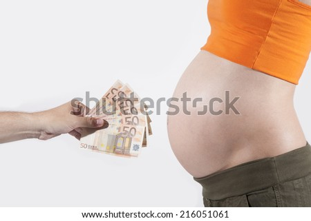 offering Euro banknotes to tummy of naked pregnant woman