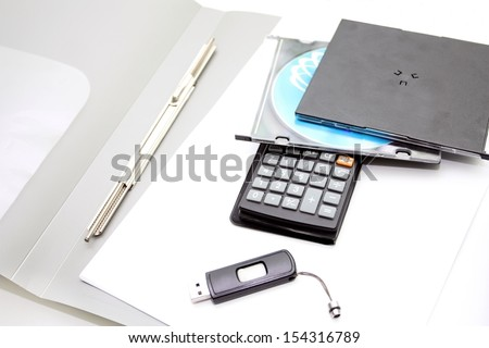 Office accessories - the folder, the calculator, and compact disks on a white background
