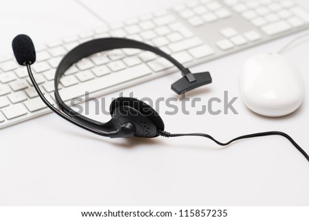 Office black headphones laying on white keyboard isolated - stock photo