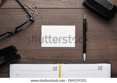 office brown wooden table with pen glasses and notebook background - stock photo