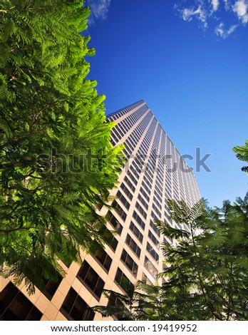 office building behind green trees - stock photo
