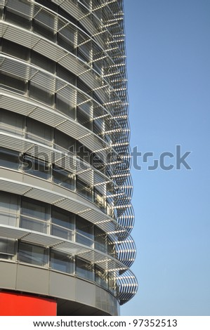 Office building behind the blue sky. The building has a gray glass facade with aluminum panels and visors. Prague, Czech Republic - stock photo