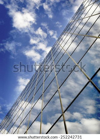 Office building details reflecting blue sky and clouds in windows - stock photo