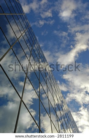 Office building details reflecting, blue sky and clouds in windows
