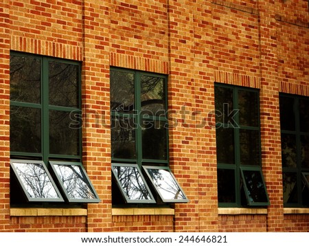 Office building details reflecting sky and clouds in windows - stock photo