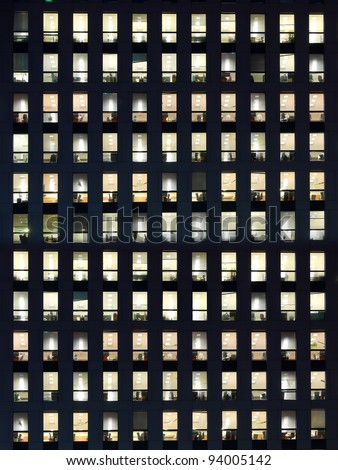 Office building exterior in the late evening with interior lights on - stock photo
