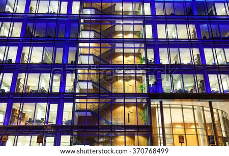Office building exterior with people at work at night - stock photo