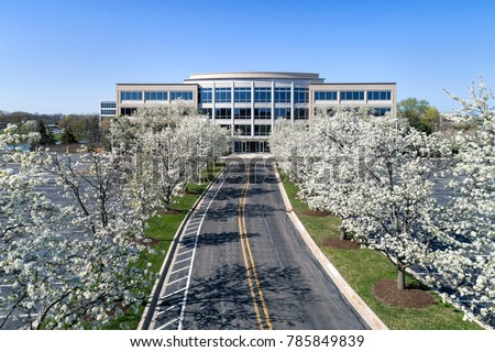 Office building headquarters in office park during spring with flowering trees.
