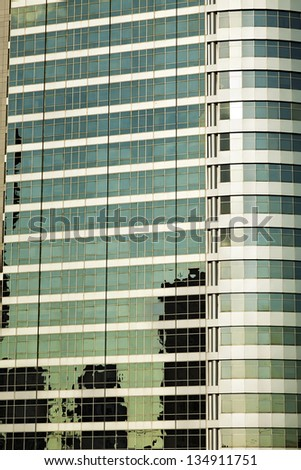 Office building's curtain wall reflects and distorts the colorful dusk skies. - stock photo