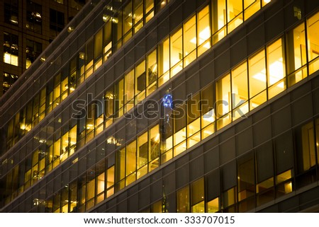 Office building windows lit up at night - stock photo
