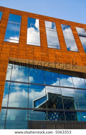 office building windows reflecting clouds and buildings