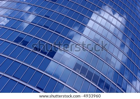 Office building windows reflecting cloudy sky