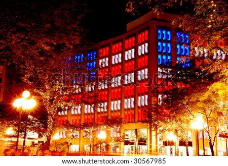 office building with the american flag lighting in the evening - stock photo