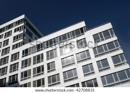office building with white walls on blue sky - stock photo