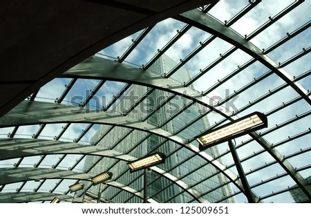 Office buildings in Canary Wharf seen from london tube station glass roof - stock photo